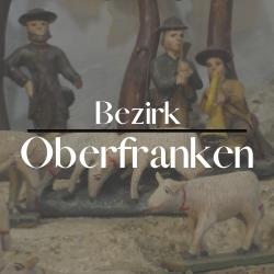 """Button mit der Aufschrift """"Bezirk Oberfranken"""" im Hintergrund sieht man 3 menschliche Figuren und 4 Schafe"""
