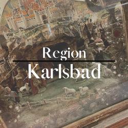 """Button mit der Aufschrift """"Region Karlsbad"""" im Hintergrund sieht man eine Kastenkrippe mit vielen kleinen Einzelteilen. Eine Höhle, davor eine Wiese und darüber erbaut sich eine große Burg."""
