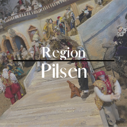 """Button mit der Aufschrift """"Region Pilsen"""" im Hintergrund sieht man eine Treppe auf dieser sich verschiedene Figuren tummeln."""