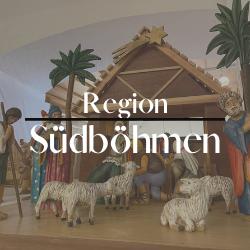 """Button mit der Aufschrift """"Region Südböhmen"""" im Hintergrund zeigt sich eine Krippe mit Palmen, Schafen und einzelnen Figuren."""